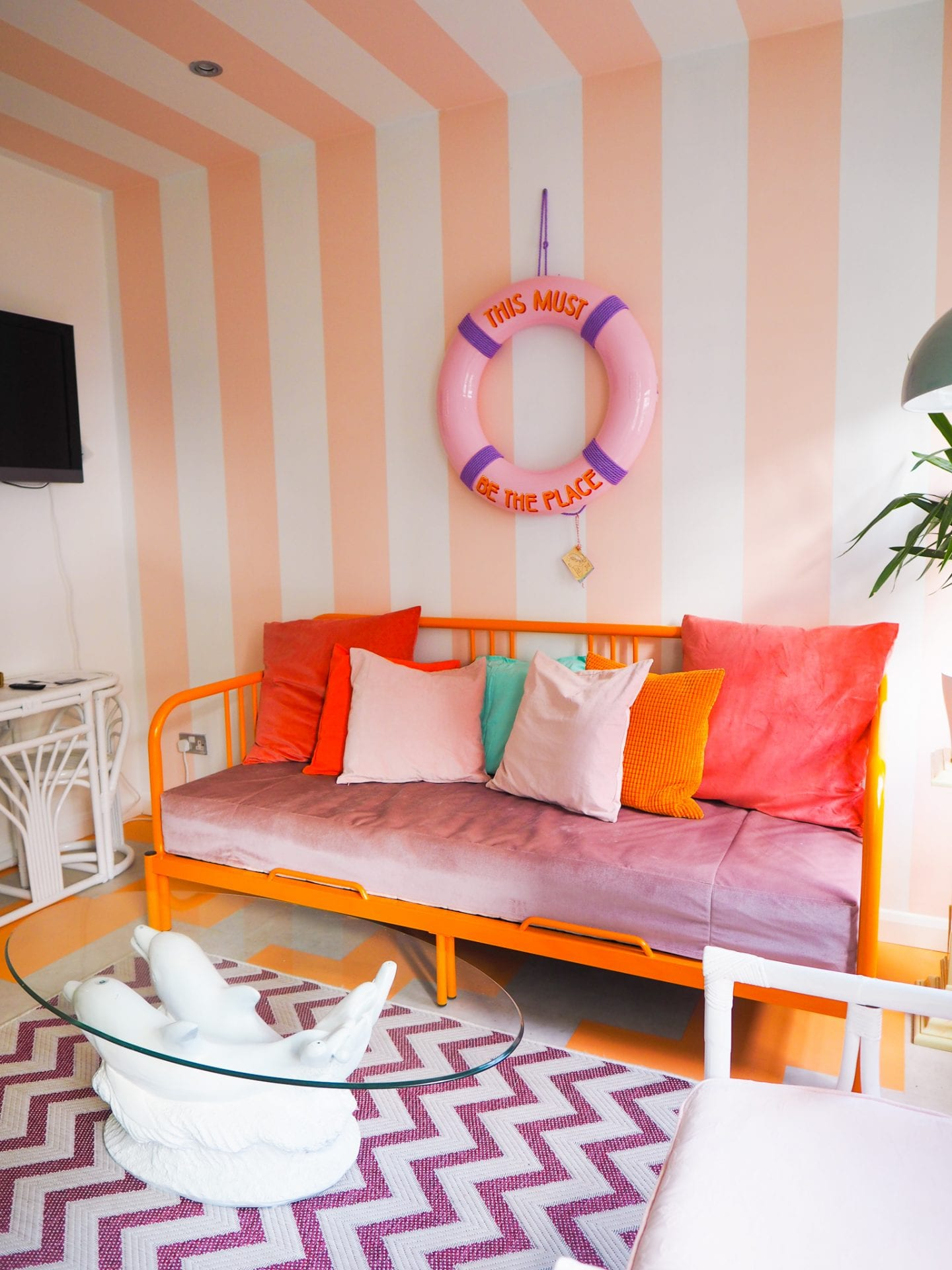 Margate-suites-hotel-airbnb-holiday-cottage-orange-sofa-bed-pink-and-white-striped-walls